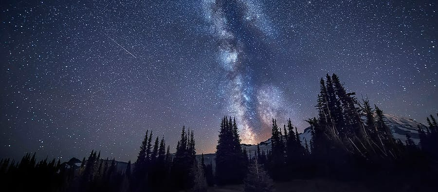 The Milky way galaxy and a shooting star over Mount Rainier in Washington State